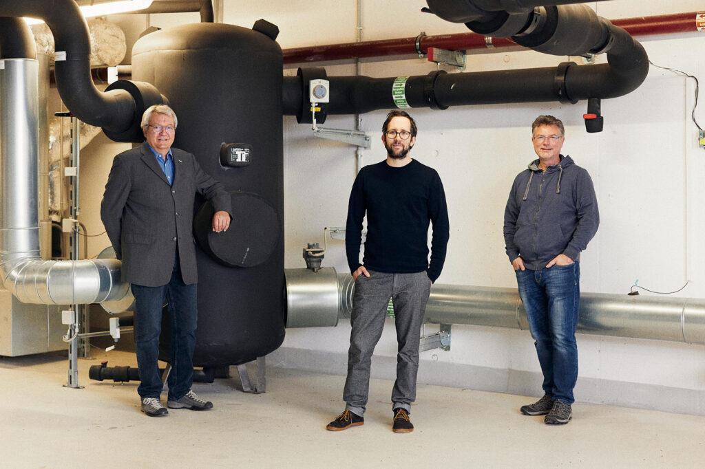 Drei Männer stehen in einem Heizungskeller vor einem großen Kessel und Rohren