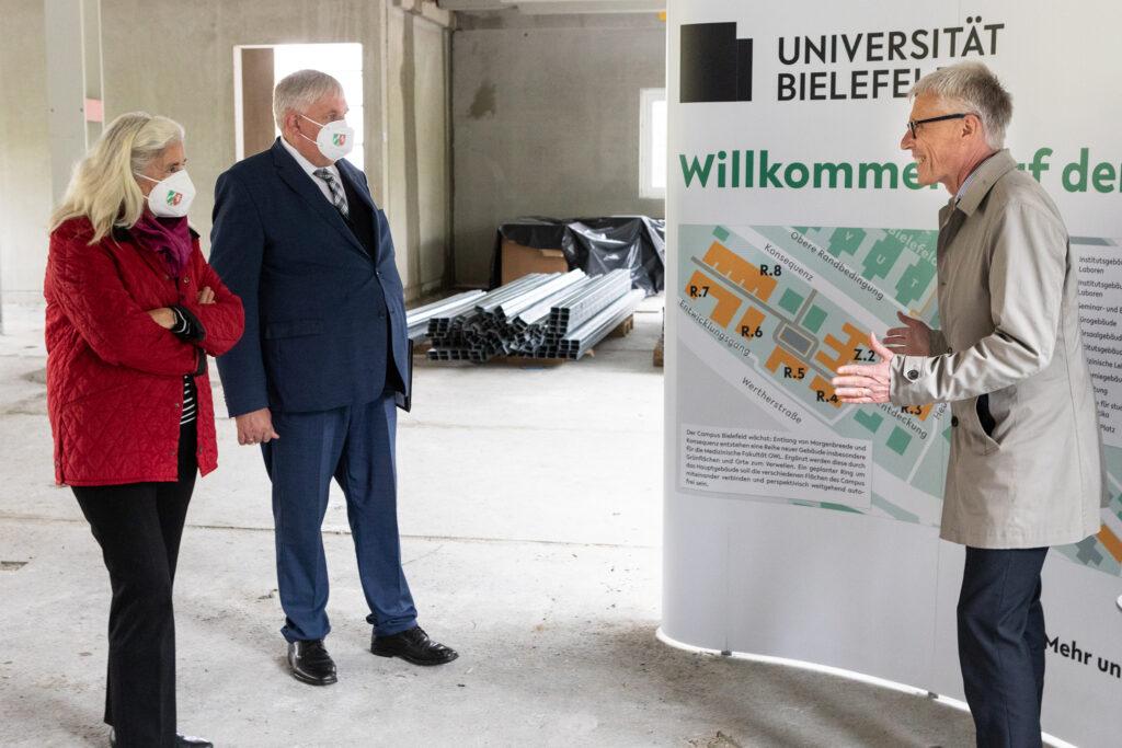 Kanzler Dr. Stephan Becker (r.) präsentiert Wissenschaftsministerin Isabel Pfeiffer-Poensgen und Gesundheitsminister Karl-Josef Laumann den Stand der Baumaßnahmen auf dem Campus Süd.