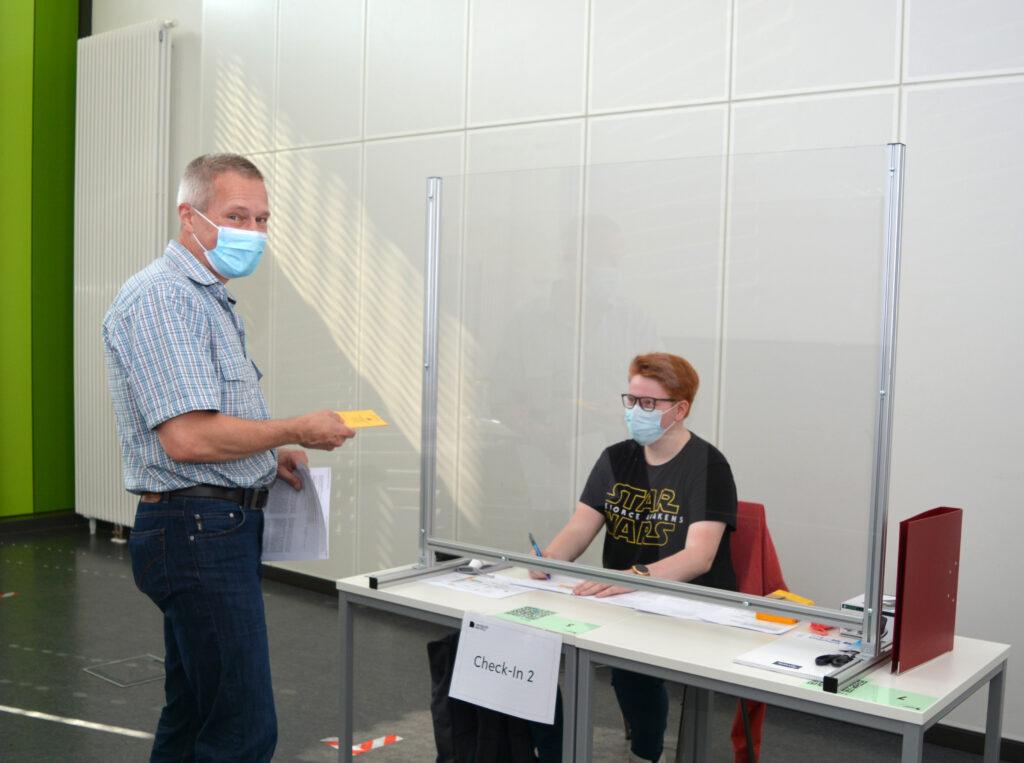 Dr. Joe Max Risse aus der Technischen Fakultät bei der Registrierung im Check-In durch die Auszubildende Alyssa Kruse.