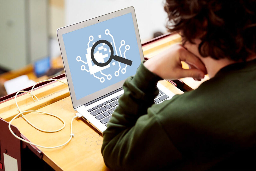 Person im Hörsaal blickt auf Notebook-Bildschirm